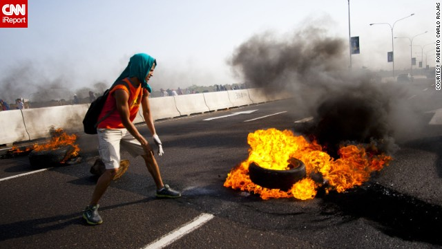 A student in Maracaibo <a href='http://ireport.cnn.com/docs/DOC-1086131'>lights a tire on fire</a> on February 15. Rojas explained this is a maneuver students use to close down streets.