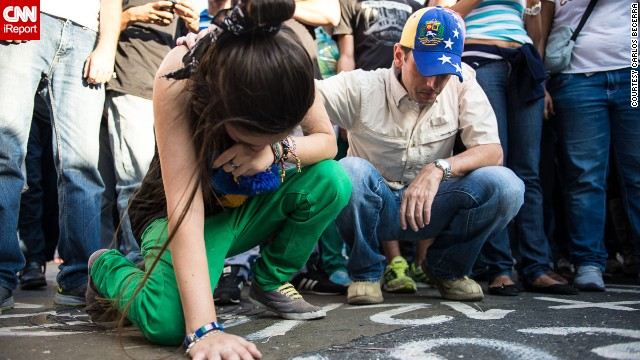 A young <a href='http://ireport.cnn.com/docs/DOC-1084811'>woman cries</a> on February 13 at the place where one of the opposition members was killed a day before in Caracas. <!-- --> </br>