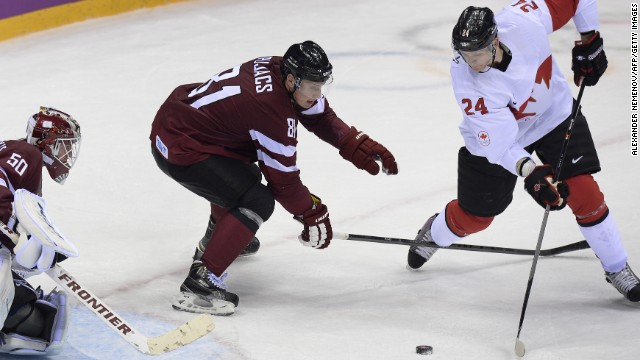 Corey Perry (R) scored in the third period to give Canada a 2-1 victory over Latvia and put the three-time defending champion through to the semifinals.