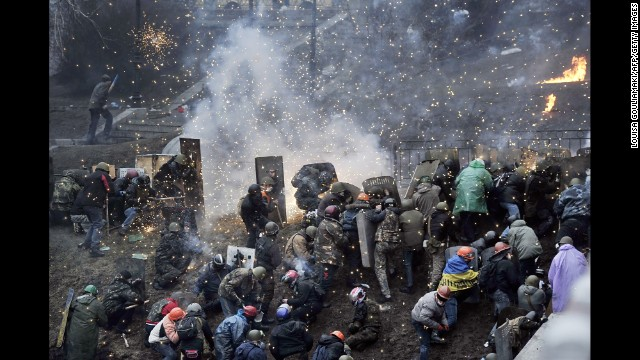 Fireworks explode over protesters near Independence Square on February 20.