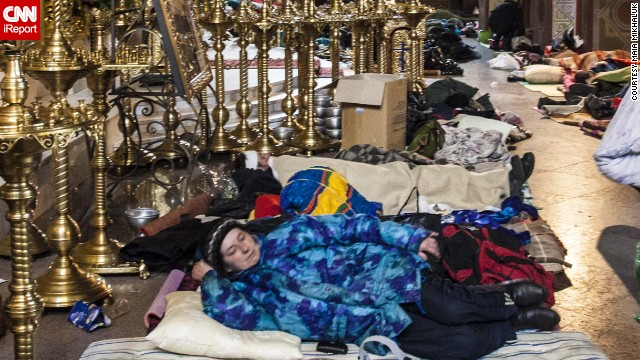 An unidentified woman takes shelter in the Mykhailovsky Cathedral in Kyiv. The cathedral opened its doors for protesters wounded during the clashes with riot police Wednesday and Thursday.