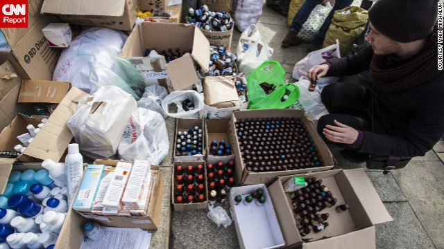 An unidentfied man sorts through items outside the Mykhailovsky Cathedral in Kyiv. The cathedral opened its doors for protesters wounded during the clashes with riot police Wednesday and Thursday.