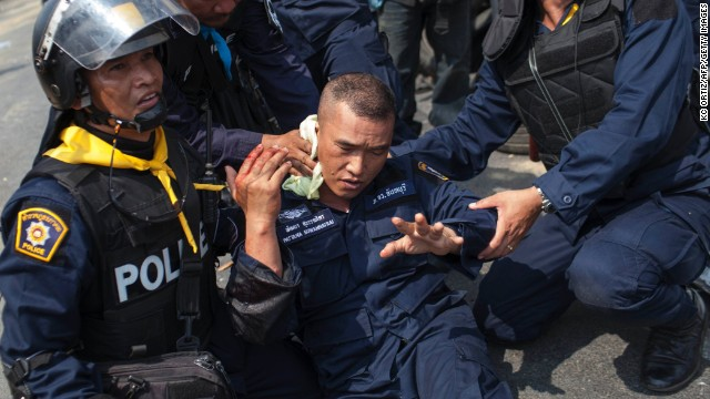 Police officers assist a colleague who was injured by a grenade thrown by protesters in Bangkok on Tuesday, February 18. At least five people were killed and more than 70 were injured in clashes during a police crackdown.
