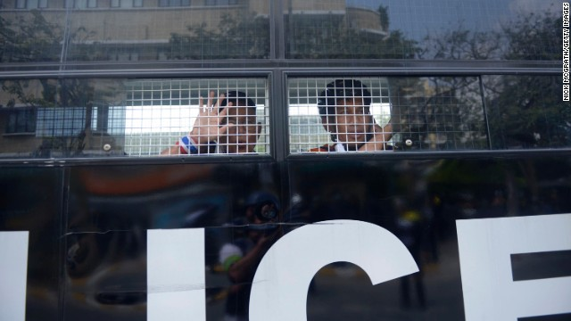 Two protesters who were arrested are taken away in a police van after clashes at Phan Fah Bridge in Bangkok on February 18. Thai police tried to reclaim the area, which anti-government protestors had been occupying for weeks, but were eventually forced to retreat after a grenade explosion and sporadic gunfire.