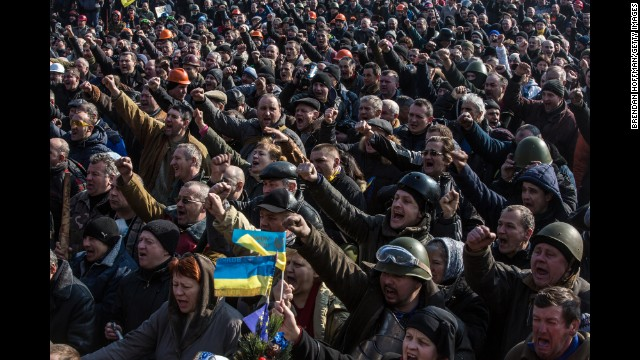 Protesters cheer after news of an agreement between the opposing sides in Kiev on February 21.