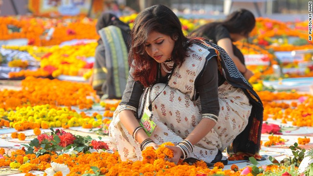 FEBRUARY 21 - DHAKA, BANGLADESH: A Bangladeshi woman decorates the Shaheed Minar, or Martyr's Monuments, on International Mother Language Day. A number of students died during the movement in 1952, defending the recognition of Bangla as a state language of the former East Pakistan, now Bangladesh. The day is now observed across the world to promote linguistic and cultural diversity and multilingualism.