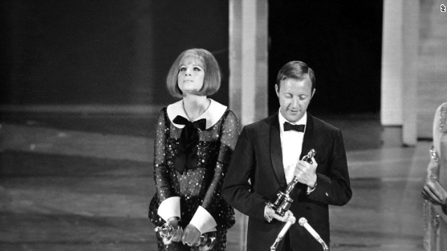 "In 1969 the Academy makes history with a tie: Barbra Streisand is named best actress for her role in ""Funny Girl"" and Katharine Hepburn for her role in ""The Lion In Winter."" Streisand is seen here beside British director Anthony Harvey, who accepts the award on Hepburn's behalf."