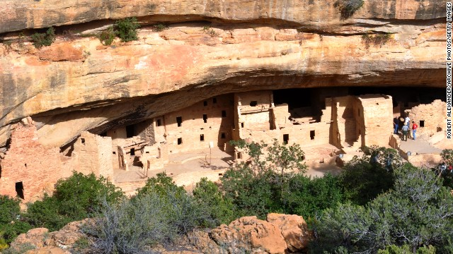 A trail leads visitors to the Spruce Tree House ruins in Mesa Verde National Park. The park's stone and adobe cliff dwellings were built by Ancestral Puebloans from the 1190s to the late 1270s.