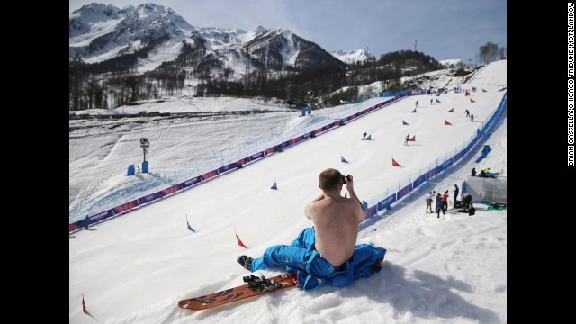 A course worker takes his shirt off to enjoy warm weather during the snowboard parallel slalom competition on February 22.