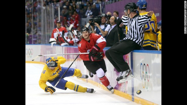 Chris Kunitz of Canada delivers a high stick to Marcus Kruger of Sweden during the hockey game on February 23.