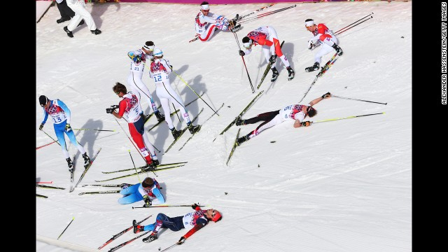 Skiers collapse on the snow after the men's 50-kilometer mass start free on February 23.