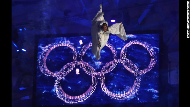 A performer hangs from a wire in front of the Olympic rings.