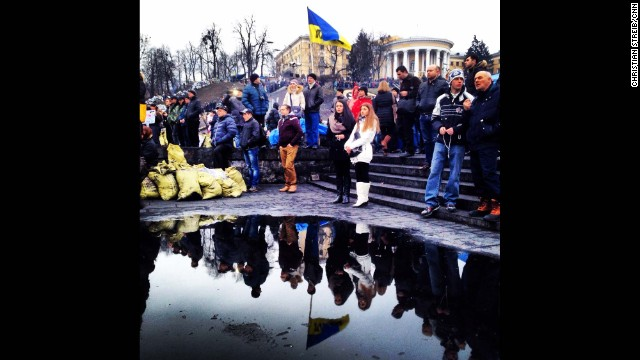 KIEV, UKRAINE: Ukrainians are reflected in a puddle as they gather to mourn the dead in Maidan Square on February 23, after protesters succeeded in forcing President Viktor Yanukovich out of office. Photo by CNN's Christian Streib. Follow Christian on Instagram at <a href='http://instagram.com/christianstreibcnn' target='_blank'>instagram.com/christianstreibcnn</a>.
