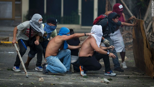 Anti-government protesters take cover during clashes with riot police in Caracas on February 22.