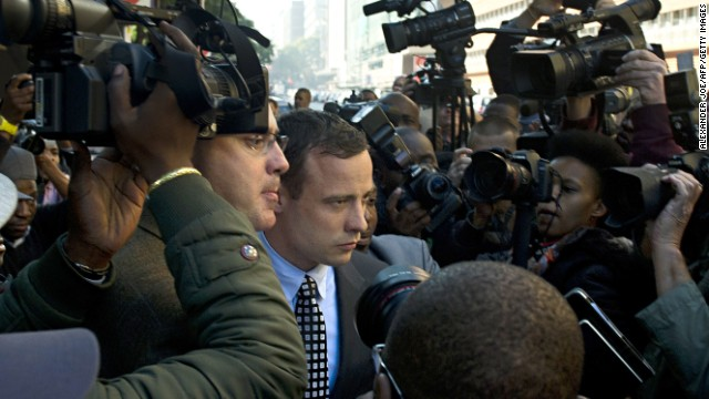 Pistorius, swamped by the press, leaves a Pretoria courtroom in June.