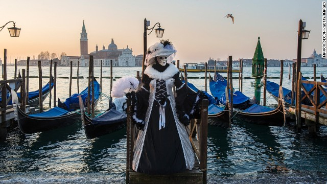 FEBRUARY 25 - VENICE, ITALY: A woman dressed in carnival costume poses in front of gondolas in Saint Mark's Square. The 2014 Carnival of Venice will run from February 15 to March 4 and includes a program of gala dinners, parades, dances, masked balls and music events.