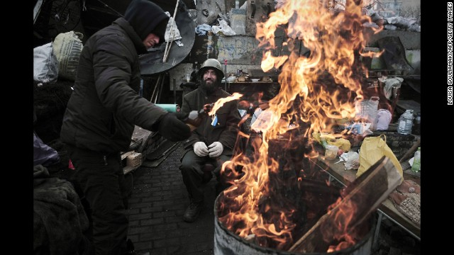 A man adds fuel to a fire at a barricade in Independence Square on February 27. Dozens of people were killed last week during clashes between security forces and protesters.