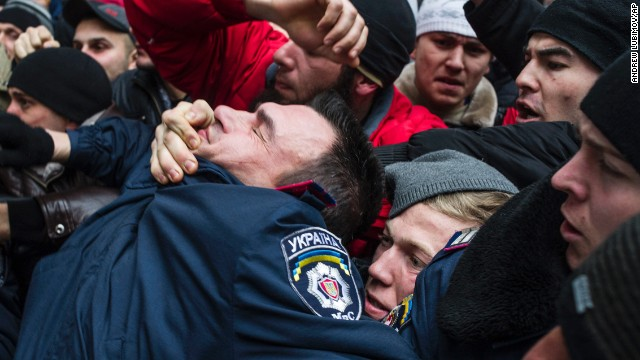 A police officer gets pulled into a crowd of Crimean Tatars in Simferopol on February 26. The Tatars, an ethnic minority group deported during the Stalin era, is rallying in support of Ukraine's interim government.