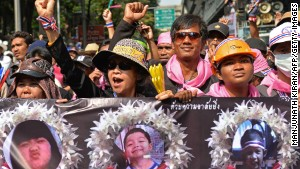Anti-government protesters march holding posters of child victims of a recent bomb blast in Bangkok.