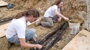 Derek Anderson and Forrest Follet remove the soil from the lid of one the graves.