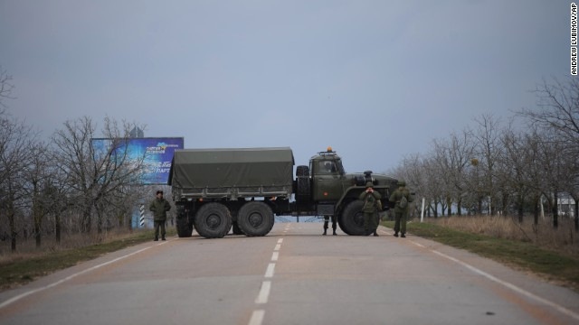 Russian troops block a road February 28 toward the military airport in Sevastopol, Ukraine, on the Black Sea coast. The Russian Black Sea Fleet is based at the port city of Sevastopol. Ukraine suspects Russia of fomenting tension in the autonomous region of Crimea, which might escalate into a bid for separation by its Russian majority.