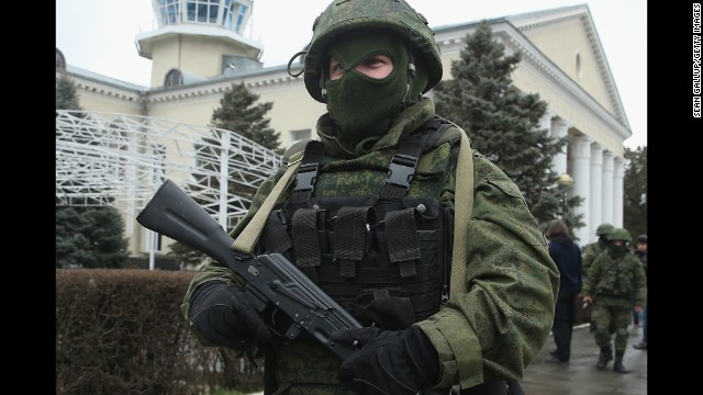 An armed man wearing no identifying military insignia patrols outside Simferopol International Airport on February 28.