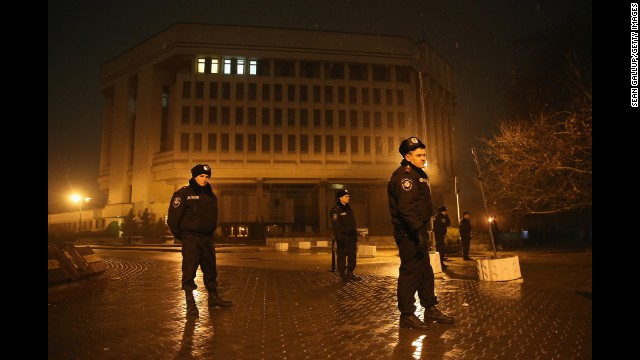 Police stand guard outside the Crimea regional parliament building in Simferopol on Thursday, February 27. Armed men seized the regional government administration building and parliament in Crimea.