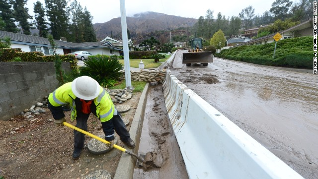 A worker clears mud from behind a retaining wall in Glendora on February 28.