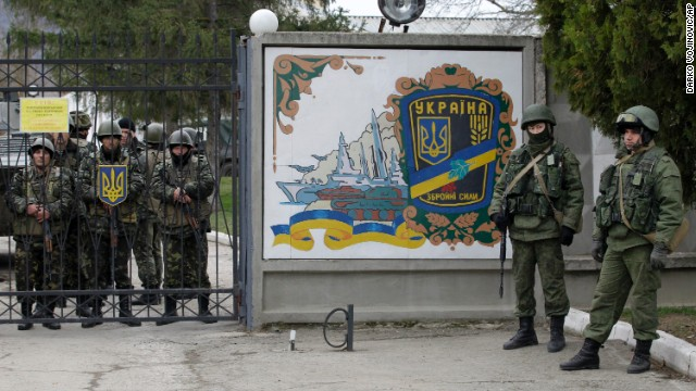 Ukrainian soldiers, left, and unidentified gunmen, right, stand at the gate of an infantry base in Perevalnoye on March 2.