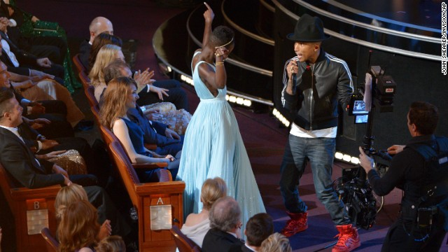 "Nyong'o dances with Pharrell Williams during his performance of ""Happy."""