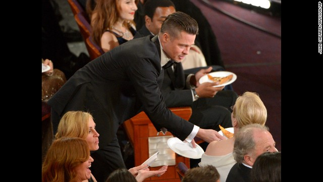 Brad Pitt passes a slice of pizza to Meryl Streep after host Ellen DeGeneres took orders from the crowd.