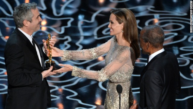 "Angelina Jolie and Sidney Poitier present Alfonso Cuaron with the best director Oscar for ""Gravity."""