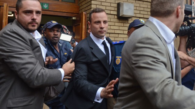 Pistorius is escorted out of the court after the first day of his murder trial in Pretoria on Monday, March 3.
