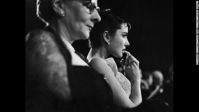 "Audrey Hepburn sits next to her mother, Baroness Ella Van Heemstra, in the audience at the Academy Awards ceremony just before Hepburn was announced winner of an Oscar for the movie ""Roman Holiday"" in 1954."