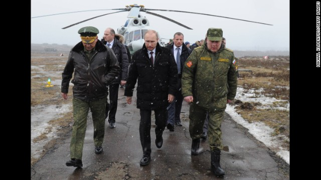 Putin, center, and Defense Minister Sergei Shoigu, left, arrive to watch a military exercise at the Kirillovsky firing ground in Russia's Leningrad region on March 3.