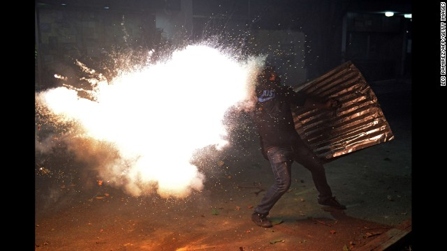 A protester tries to throw a homemade bomb during clashes with police in Caracas on March 3.
