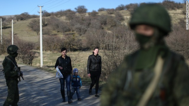 Wives of Ukrainian soldiers walk past Russian soldiers to visit their husbands guarding a military base in Perevalnoye on March 3.