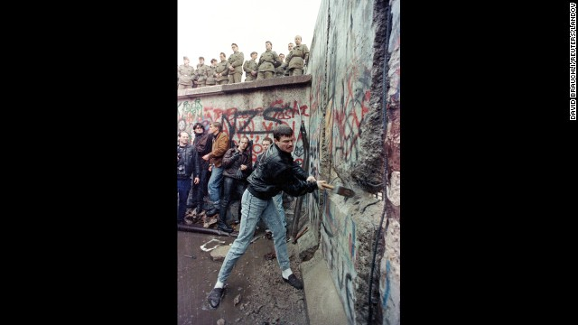 A demonstrator pounds away at the Berlin Wall as East Berlin border guards look on from above the Brandenburg Gate on November 11, 1989. Gorbachev renounced the Brezhnev Doctrine, which pledged to use Soviet force to protect its interests in Eastern Europe. On September 10, Hungary opened its border with Austria, allowing East Germans to flee to the West. After massive public demonstrations in East Germany and Eastern Europe, the Berlin Wall fell on November 9.