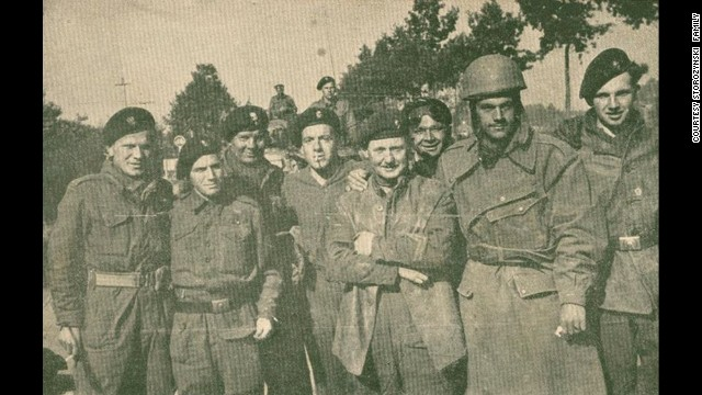 Dionizy Storozynski, wearing a helmet, poses with members of his regiment -- the Polish 24 Lancers -- during the invasion of Normandy, near Abbeville, France. <!-- --> </br>He was a motorcycle scout.