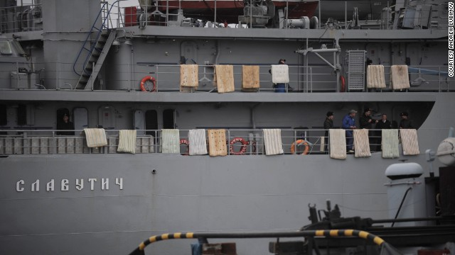 People stand on the Ukrainian Navy ship Slavutich while it's at harbor in Sevastopol on March 4. Mattresses were placed over the side of the ship to hinder any attempted assault.