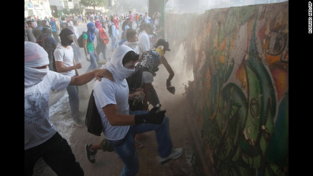 Protesters destroy a wall for more rocks to throw at riot police in Caracas on March 4.