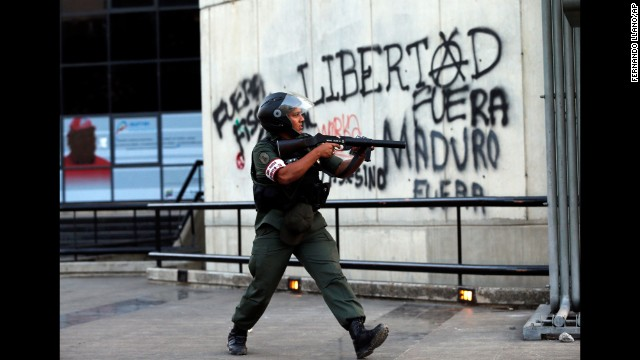 A Bolivarian National Guard officer points a tear gas launcher at demonstrators in Caracas on March 4.
