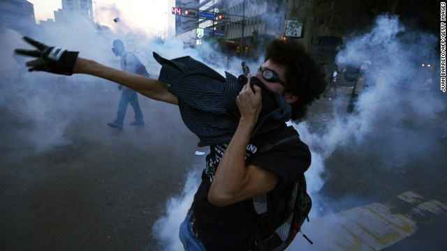 An activist throws tear gas back at riot police during a protest against the Venezuelan government in Caracas on March 5.