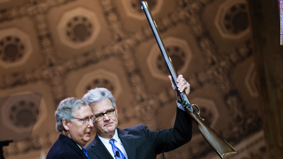 Retiring U.S. Sen. Tom Coburn, right, of Oklahoma holds a rifle given to him by Senate Minority Leader Mitch McConnell during the 2014 Conservative Political Action Conference on Thursday, March 6, in National Harbor, Maryland. Click through the images for highlights from the conference.