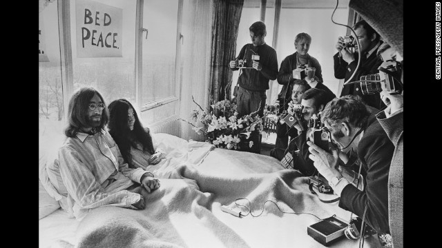 "John Lennon and Yoko Ono pose for the press at their hotel in Amsterdam, Netherlands, in March 1969. The couple stayed in bed for seven days ""as a protest against war and violence in the world."""