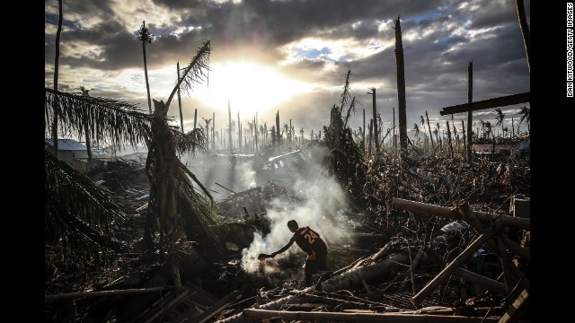 A man fans flames on a fire in Leyte, Philippines, after Typhoon Haiyan ripped through the country in November.