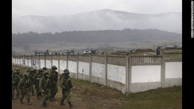 Armed men believed to be Russian military march in the village outside Simferopol on Friday, March 7.