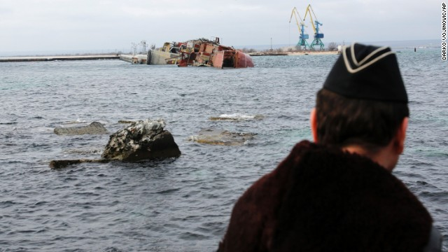 A Ukrainian Navy officer looks at the scuttled, decommissioned Russian vessel Ochakov from the Black Sea shore outside the town of Myrnyi, Ukraine, on March 6. In the early hours of the day, Russian naval personnel scuttled the ship, blockading access for five Ukrainian Naval vessels now trapped inside of the Southern Naval Headquarters.