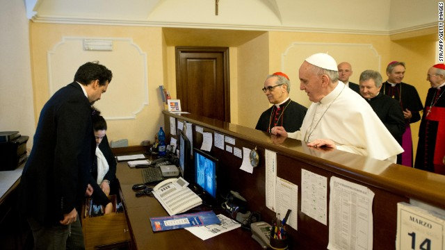 Francis stands at the reception desk of the Domus Internationalis Paulus VI residence, where he paid the bill for his stay during the conclave that would elect him leader of the world's 1.2 billion Catholics.