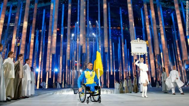 Biathlete Mykhaylo Tkachenko carries the Ukrainian flag into the stadium.